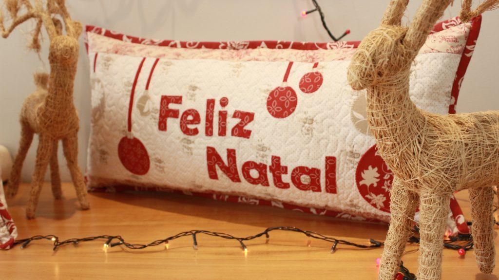 Almofada em pacthwork com escrito Feliz Natal na Técnica de patchaplique, com uma rena de palha em cada lado na cena natalina.